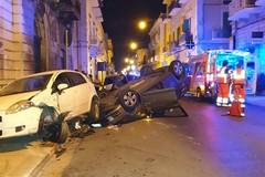 Sbandano e finiscono contro le auto in sosta, la vettura si ribalta: illesi