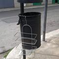 Una griglia per doccia abbandonata su un cestino portarifiuti