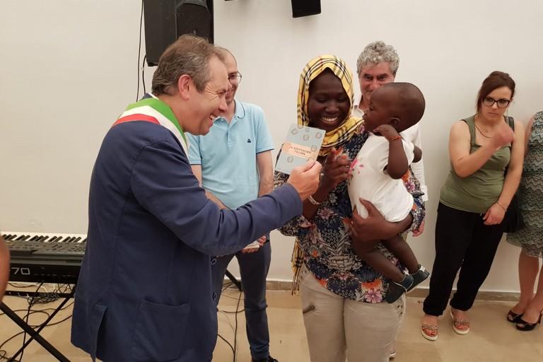 Depalma dona la Costituzione ad una bimba nata in Italia. <span>Foto Arcangelo Minenna</span>